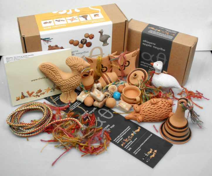 Ancient toys in a box animal figurines, bell-shaped rattle, spin-top, marbles and knucklebones